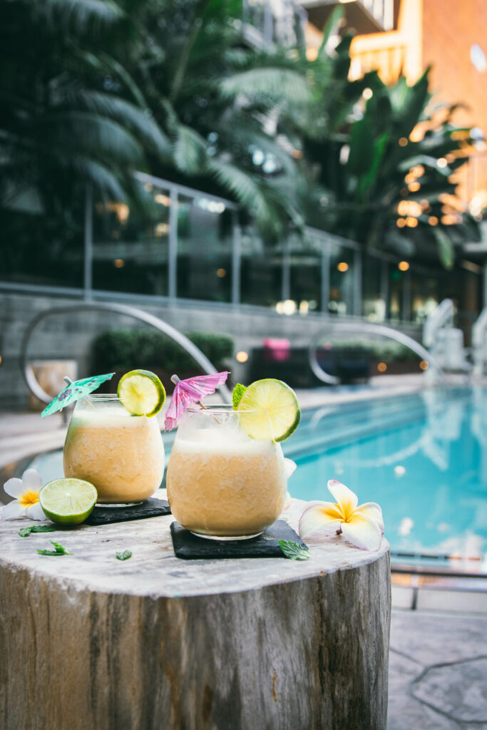 two 4 ingredient pina coladas next to a pool on a wooden stand