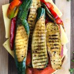 grilled veggies on top of cheese on ciabatta bread for a grilled veggie party sub