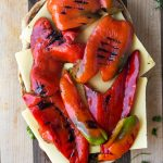 grilled peppers on top of cheese on ciabatta bread for a grilled veggie party sub