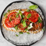 overhead shot of tomato toast with feat and basil on a black plate