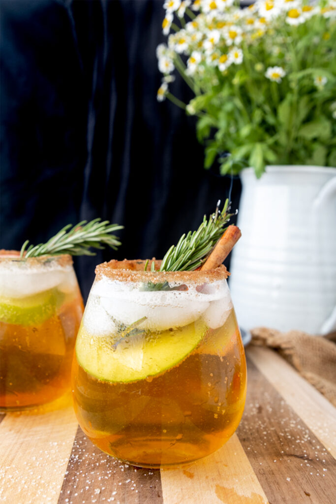 wine glass of apple cider sangria with a rosemary branch