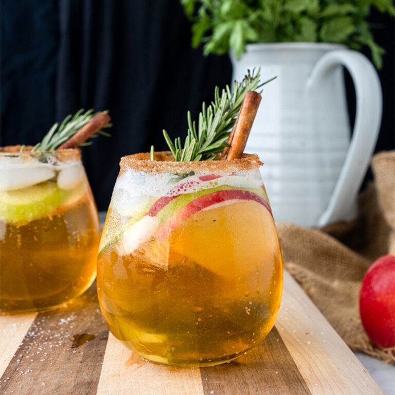 smoky apple cider sangria with cinamon, apple slices, and rosemary on a wood board