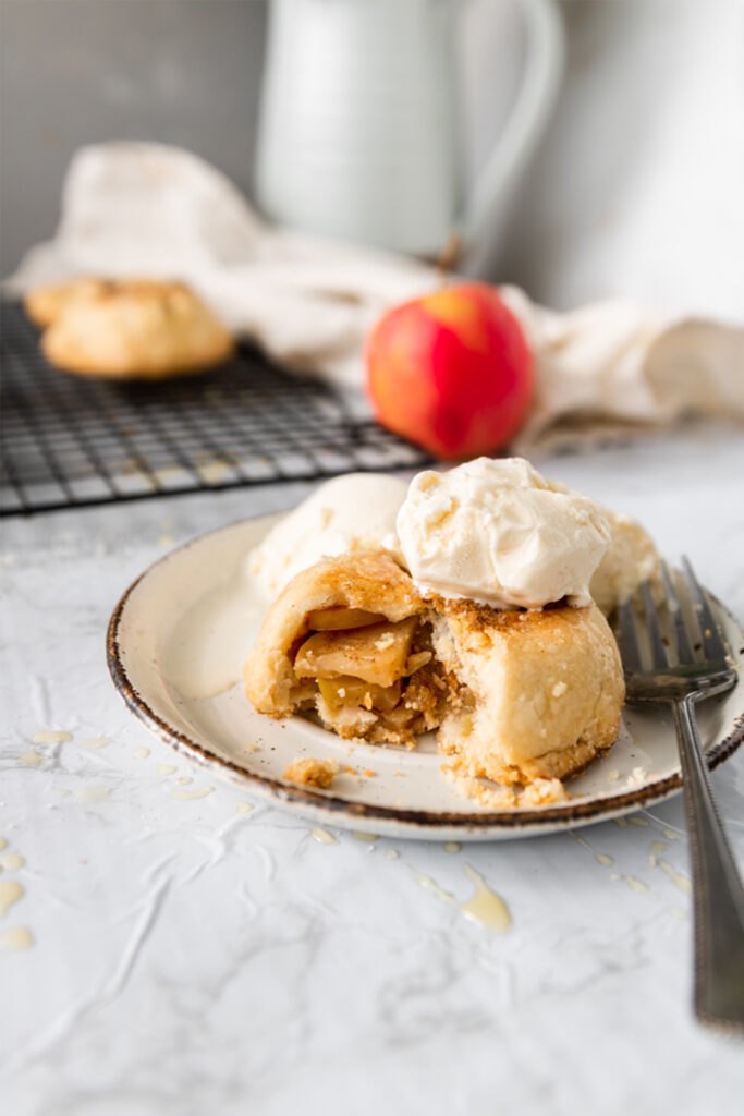 vegan apple hand pie with a scoop of vanilla ice cream on top