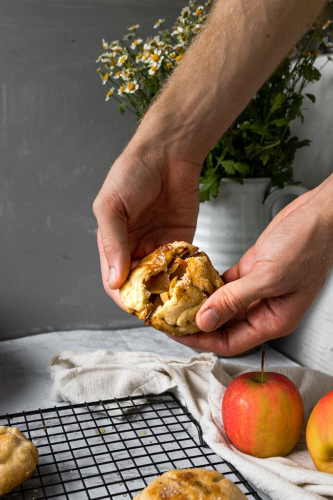 hands breaking open hand pie over top of a table