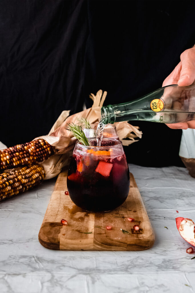 bottle pouring sparkling water into a glass of red sangria