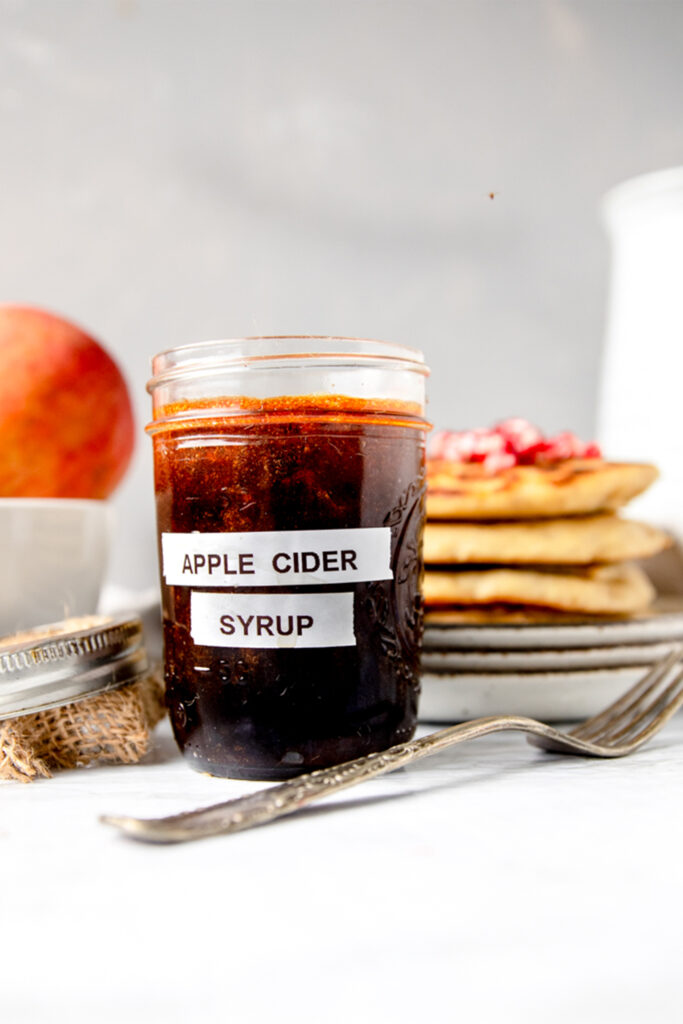 "side view of glass ball jar labeled "" apple cider syrup"" next to an antique silver fork"