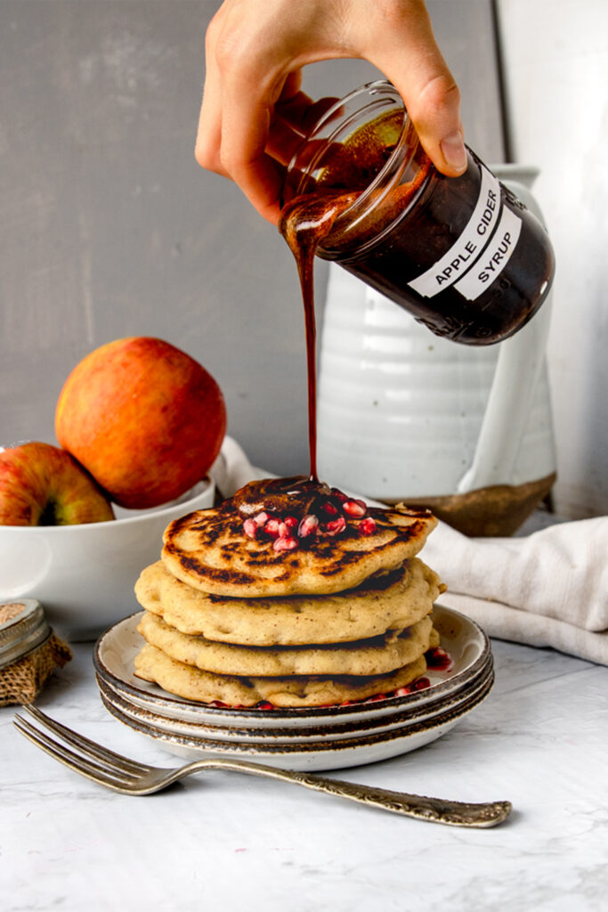 hand holding jar of boiled apple cider pouring it onto a stack of pancakes