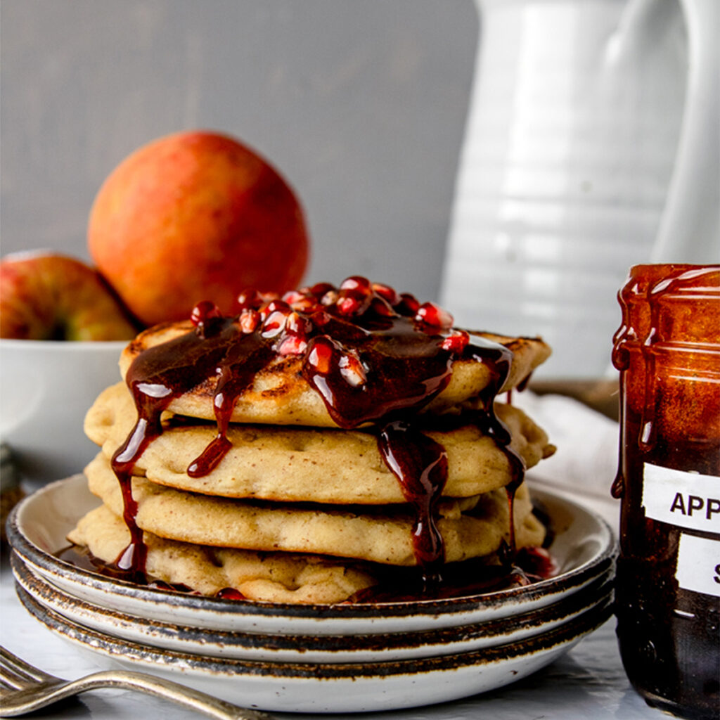 stack of pancakes with apple cider syrup dripping down