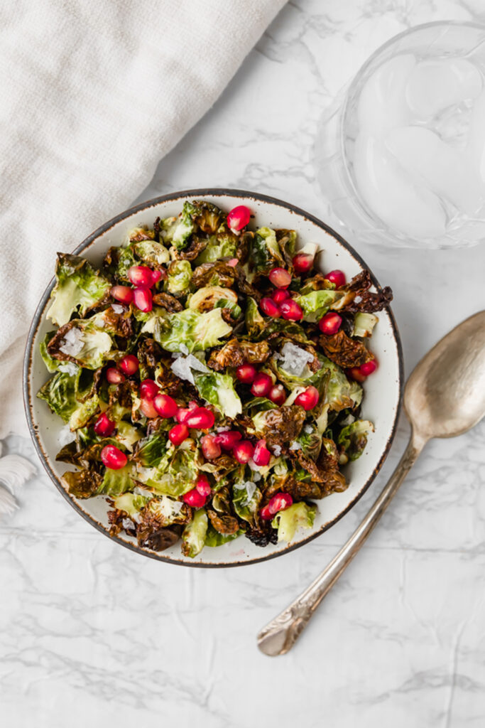 Crispy Brussels Sprout Chips, a fun salad option ready in just 15 minutes! Individual leaves of Brussels speckled with flaky sea salt and juicy pomegranate, making for a perfectly unique roasted Brussels sprouts side. This simple Thanksgiving recipe is delicious all year long!