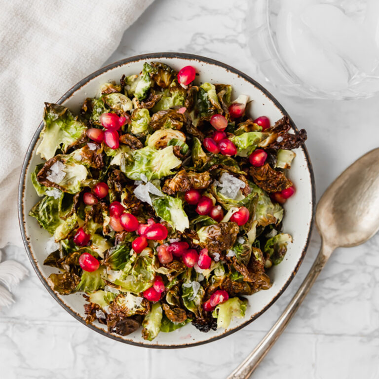 overhead shot of crisp Brussels with pomegranate on a marble board next to a silver spoon