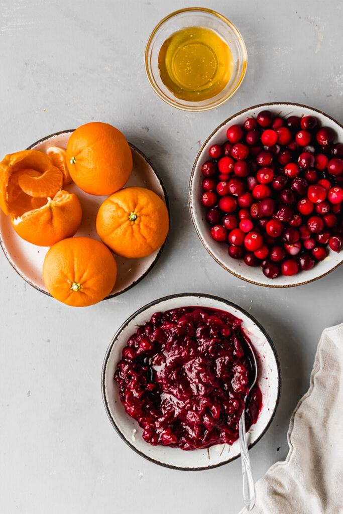 orange cranberry sauce in a white bowl next to bowls of fresh cranberries and maple syrup