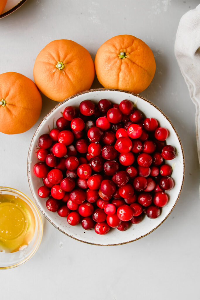 bowl of fresh cranberries in a white bowl next to some oranges