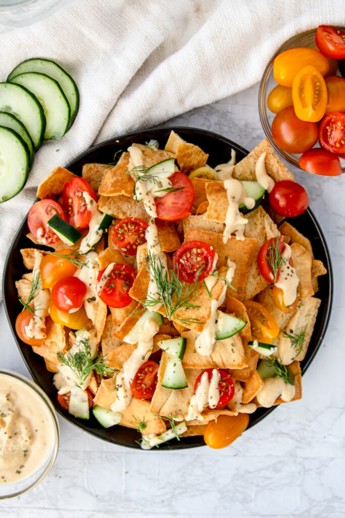 For a unique appetizer, try Mediterranean Nachos, made with pita chips and Tribe Mediterranean Hummus! They're a delicious snack for any time of day and packed with flavor. Ready in just 5 minutes and totally customizable!