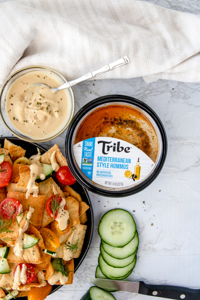 overhead shot of tribe mediterranean hummus container on a white board