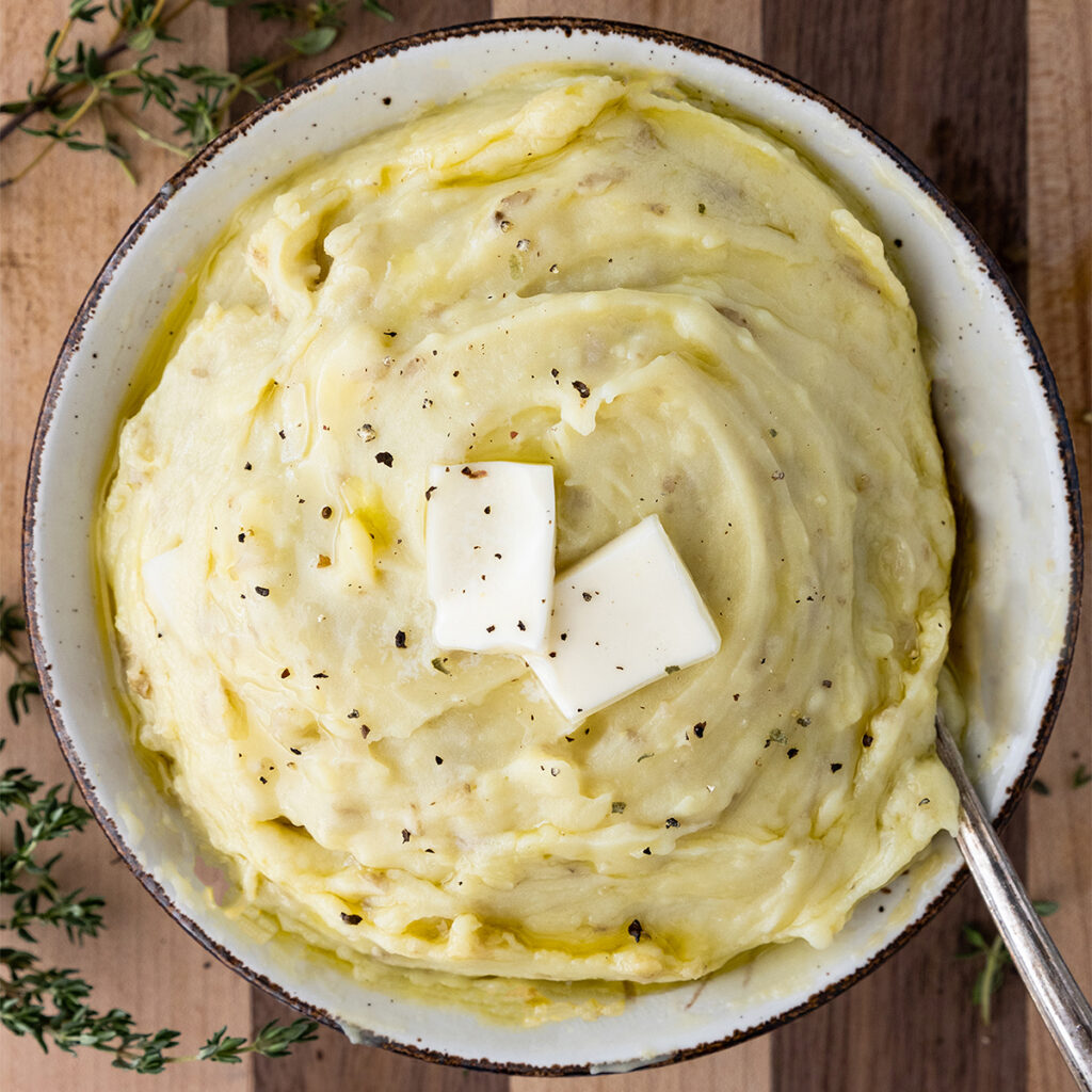 bowl of mashed potatoes with two pats of butter