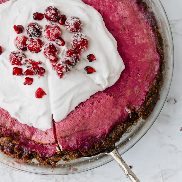 silver server grabbing a slice of pink cranberry curd pie topped with coconut cream