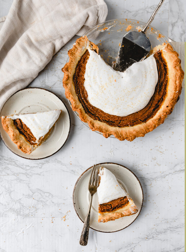 one vegan pumpkin pie with two slices on plates
