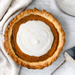 overhead shot of vegan pumpkin pie topped with coconut whipped cream