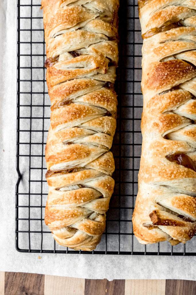 two braids of apple strudel on a cooling rack