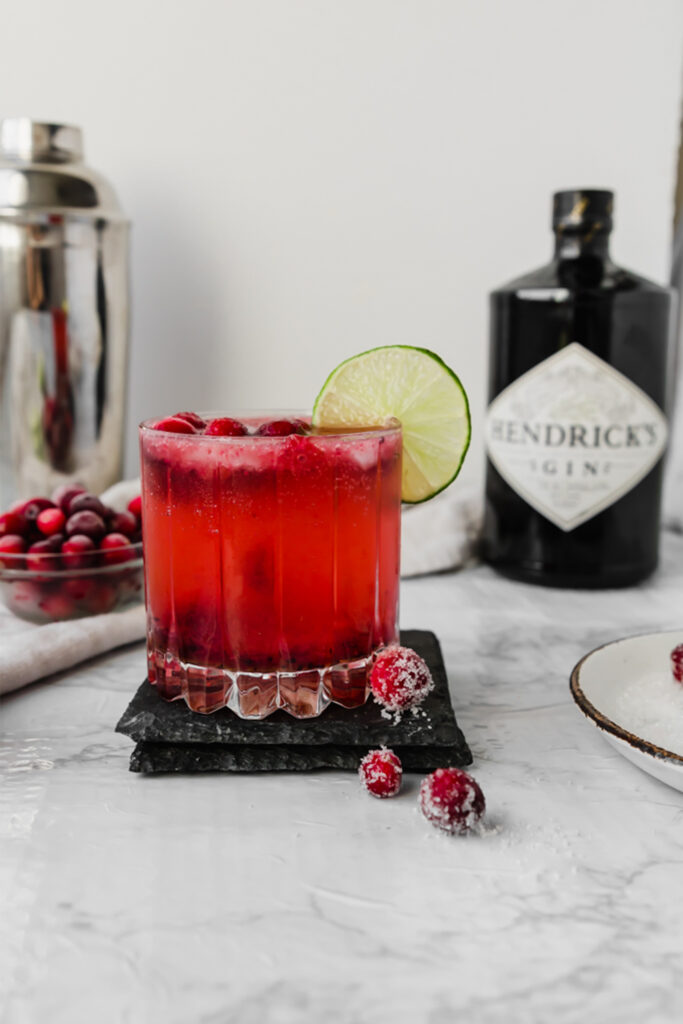 glass of cranberry gin fizz on a marble board in front of Hendricks gin