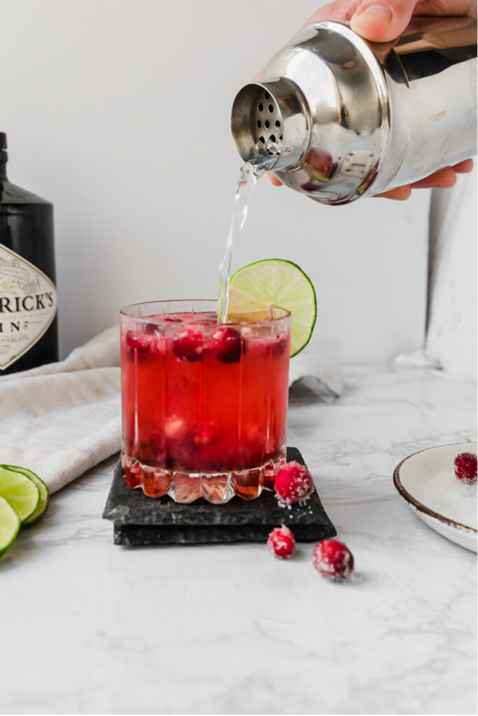 sparkling water being poured from a shaker into a cranberry gin fizz