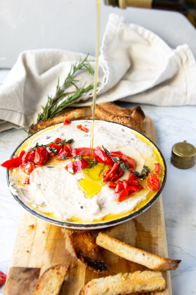 olive oil pouring into a bowl of rosemary white bean dip