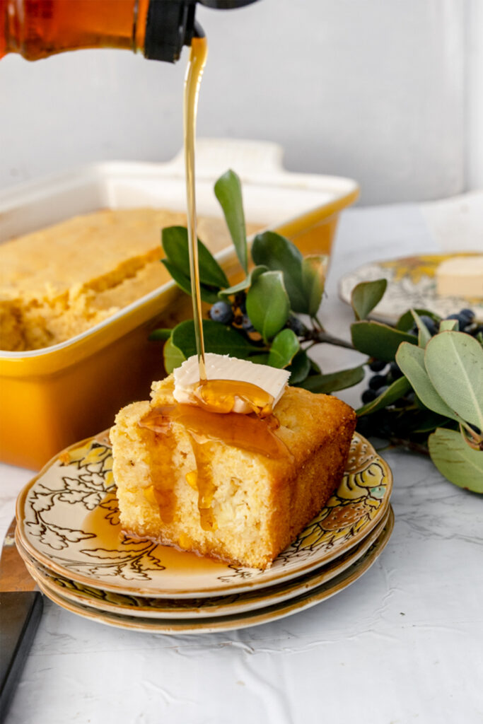 slice of fluffy cornbread on a plate with a pour of maple syrup
