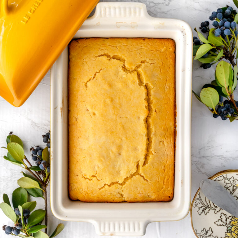 overhead shot of perfect cornbread in a le creuset ceramic yellow dish on a marble table