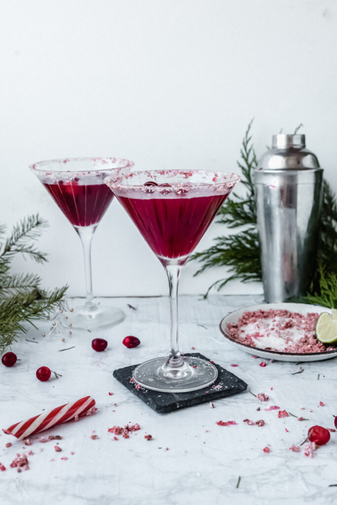two red cosmopolitans in martini glasses next to a candy cane and some pine branches