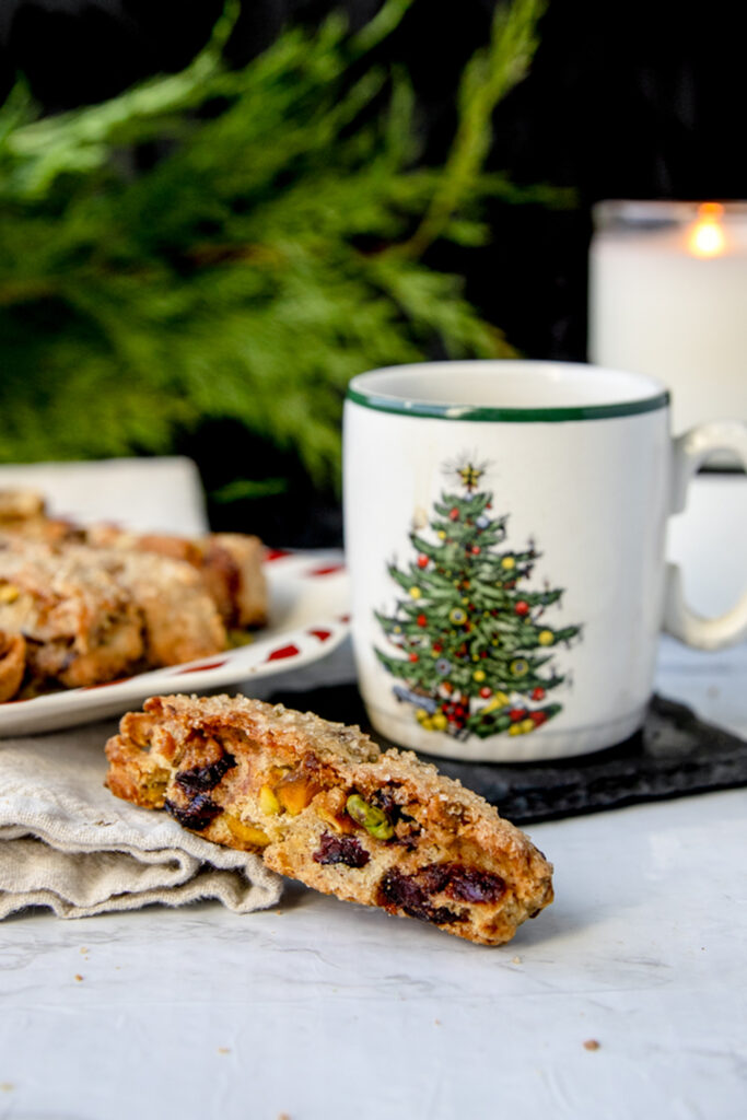 cranberry pistachio biscotti next to a christmas mug on a white table
