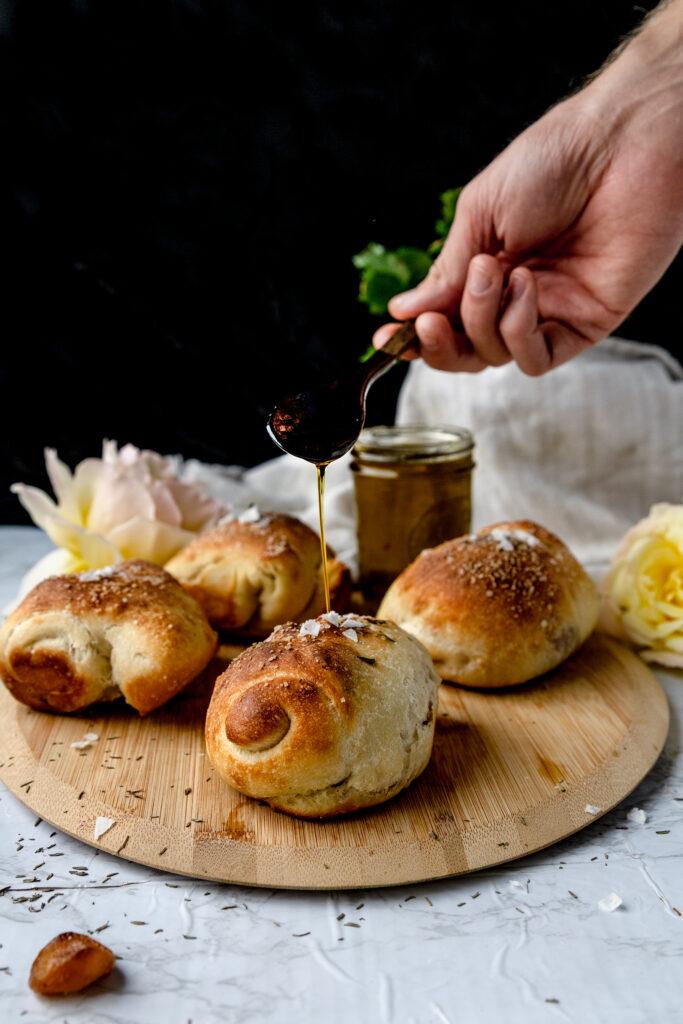 spoon drizzling olive oil onto vegan garlic bread