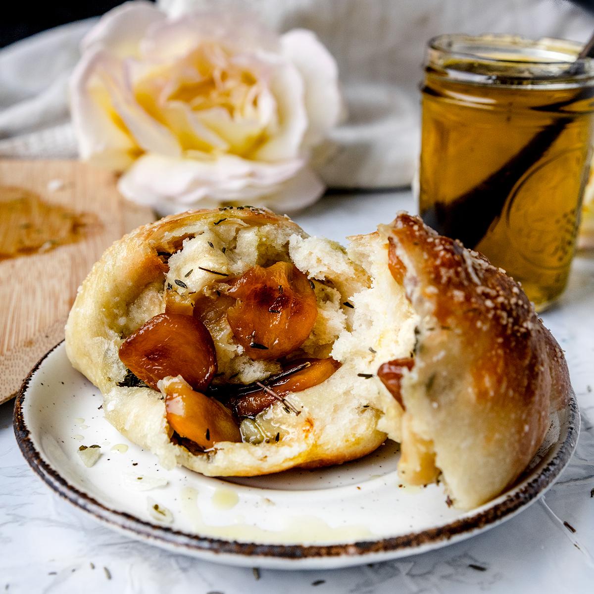 broken open garlic rolls on a white plate next to garlic olive oil in a jar