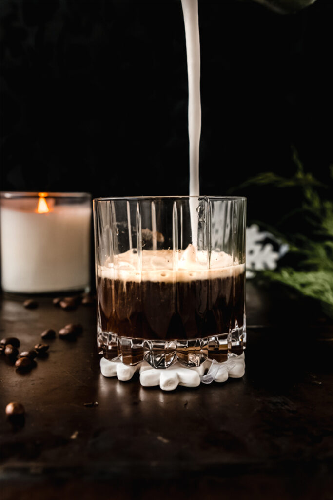 side view of a coffee cocktail with a stream of coconut cream going into it