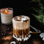 side view of vegan white Russian cocktail with gingerbread spices on dark tray