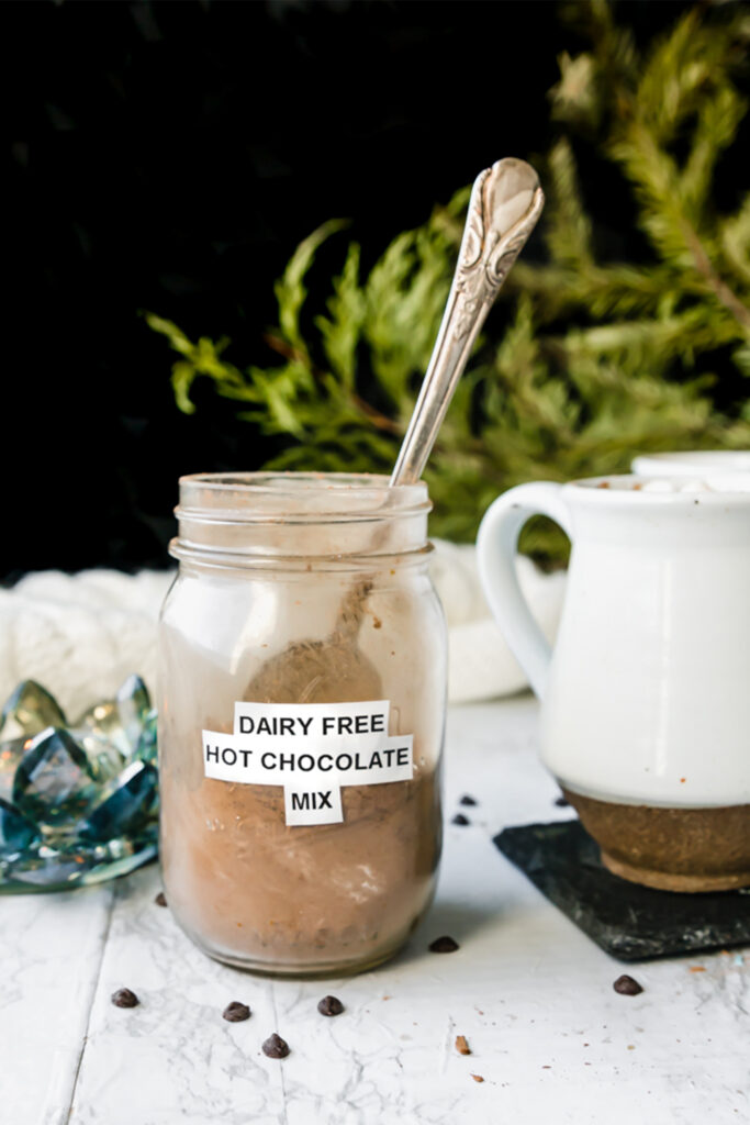 """antique spoon dipped into glass mason jar with label """"dairy-free hot chocolate mix"""""""