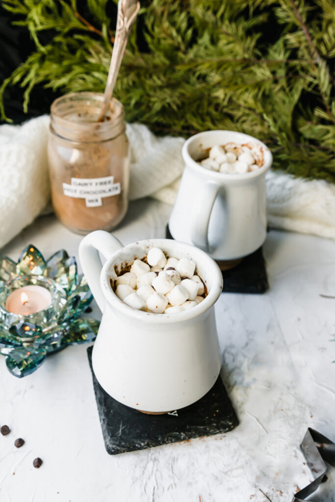 two mugs of dairy-free hot chocolate on a marble board with a candle