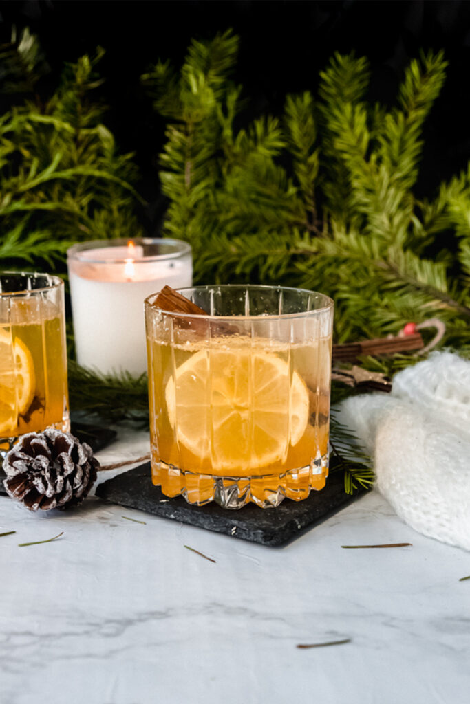 two hot toddy cocktails in front of a lit candle on a table