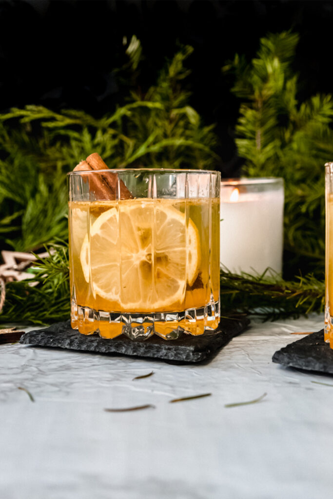 close up hot toddy with cinnamon stick and lemon round