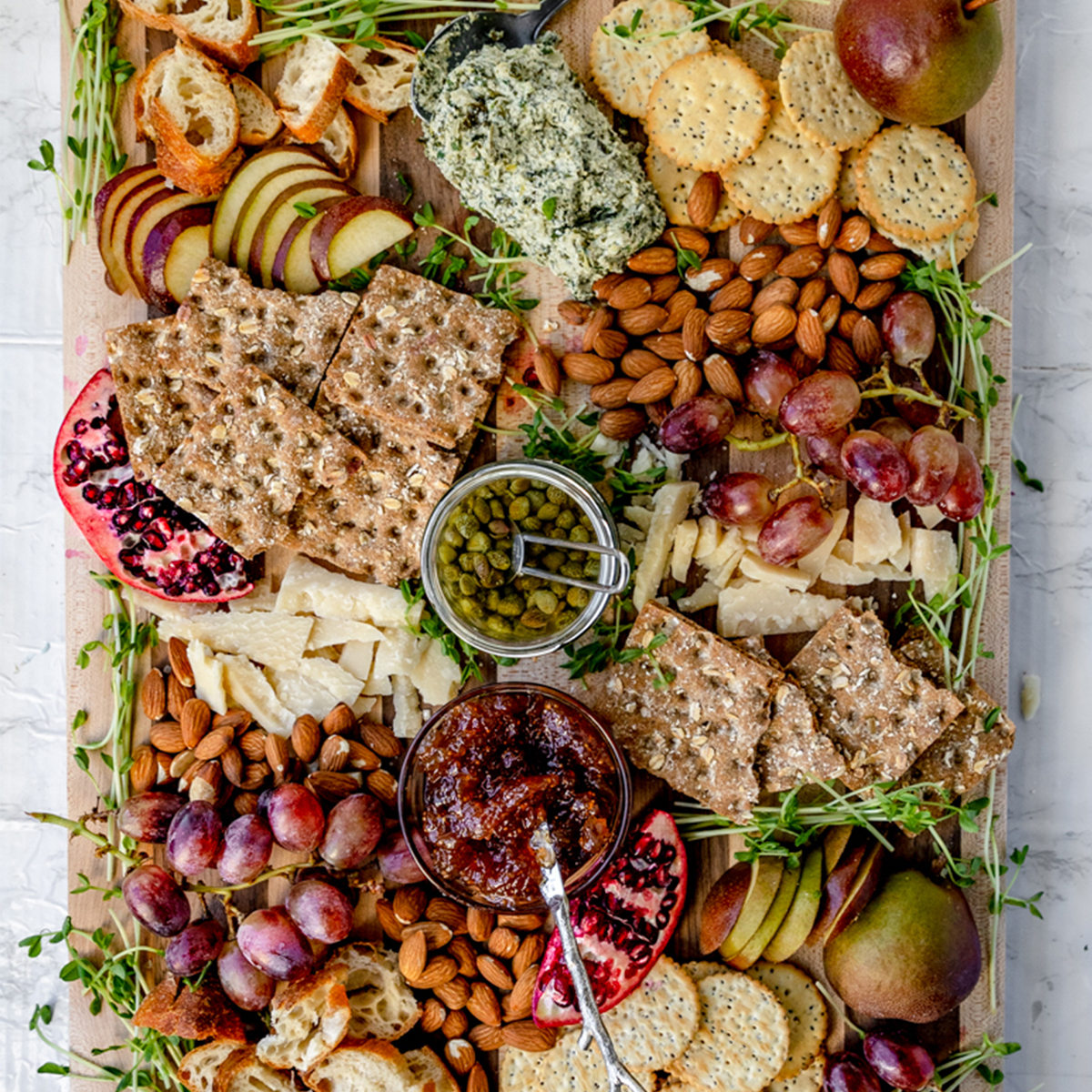 overhead shot of wooden cheese board with a variety of fruits, cheeses, and nuts in a purple green color scheme