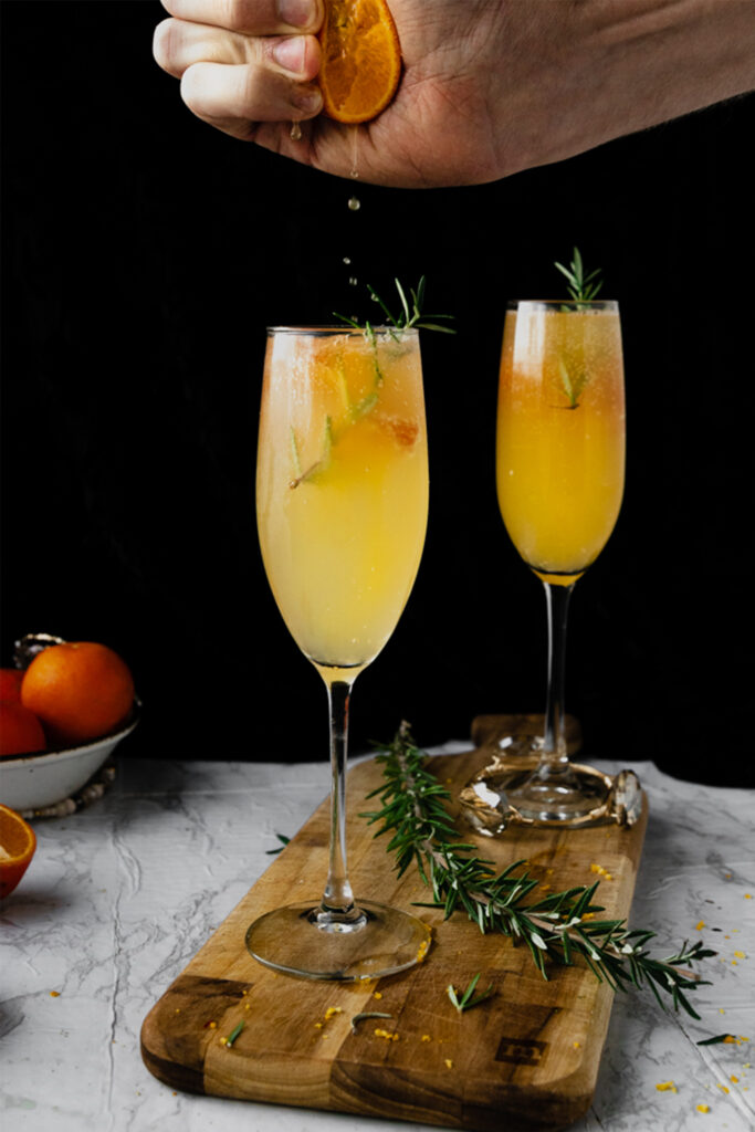 hand squeezing orange juice into champagne flute of mimosa