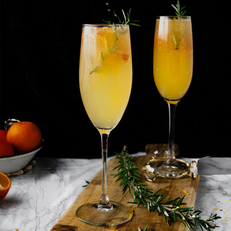 two flutes of orange mimosa cocktail on a wooden board