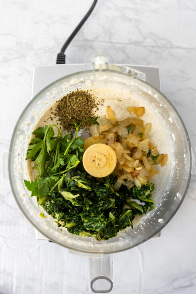 food processor filled with spinach, herbs, onions, and spices