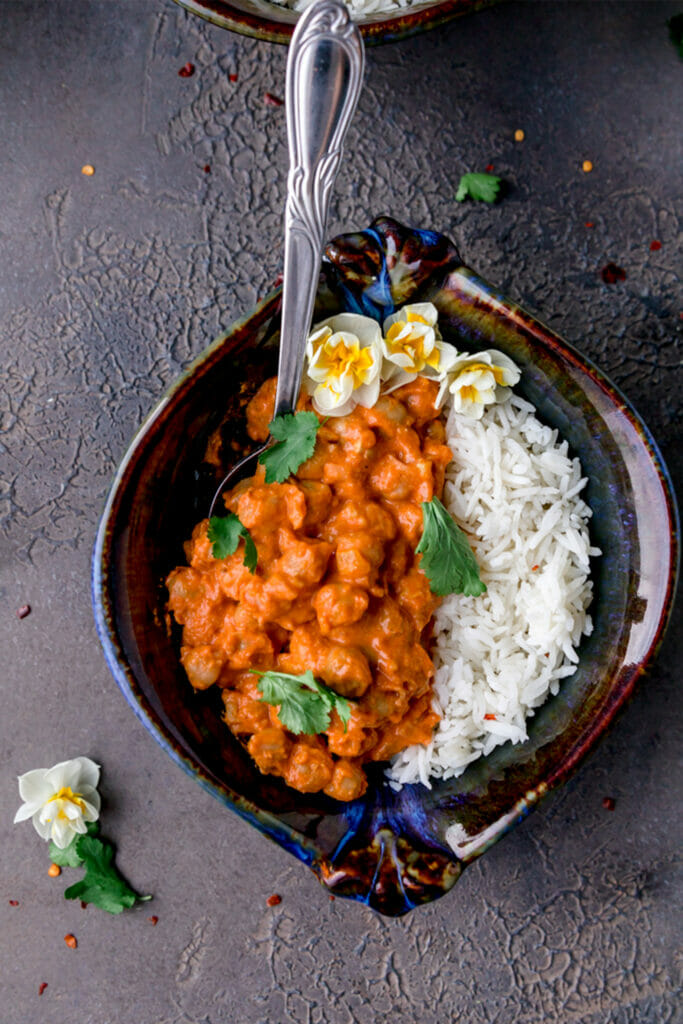 overhead shot of chickpeas in tomato butter cream sauce with basmati rice in a blue bowl