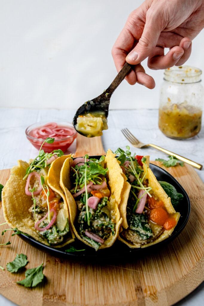 hand spooning salsa verde into three vegan tacos
