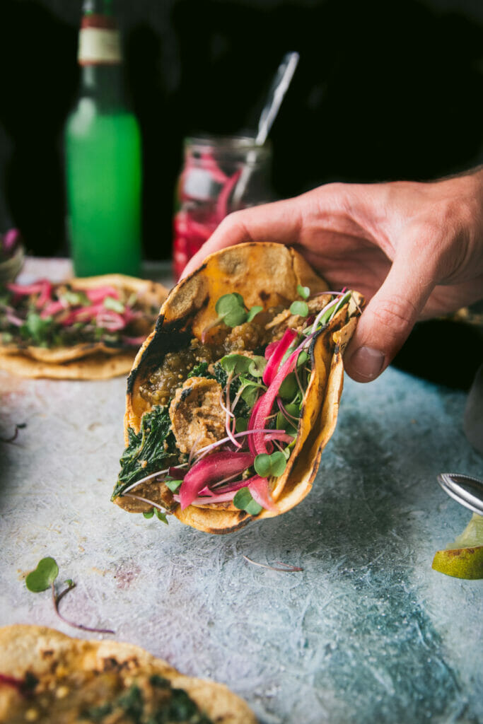 hand holding a creamy kale potato taco with pickled onions