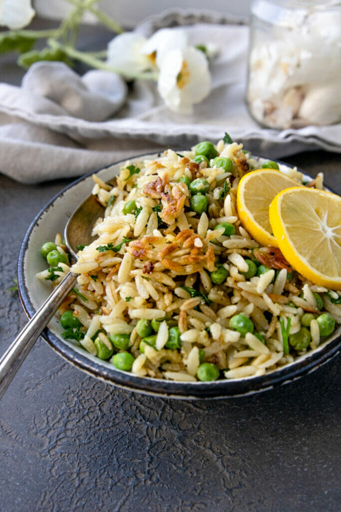 side view of crispy orzo in white bowl with silver spoon