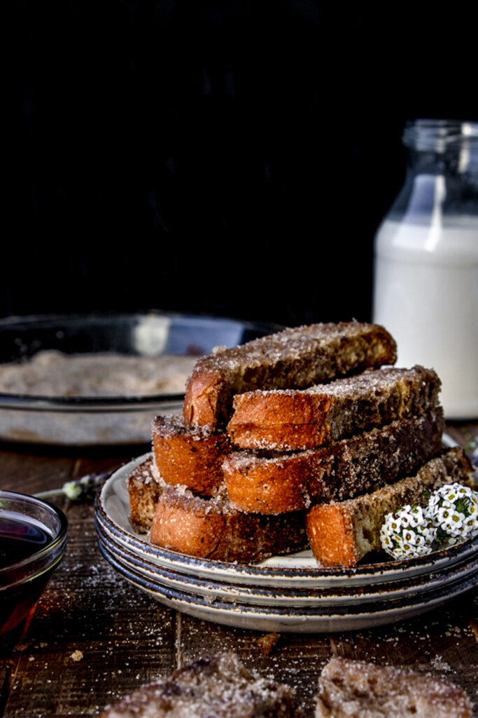 plate of cinnamon sugar french toast sticks next to a glass of milk