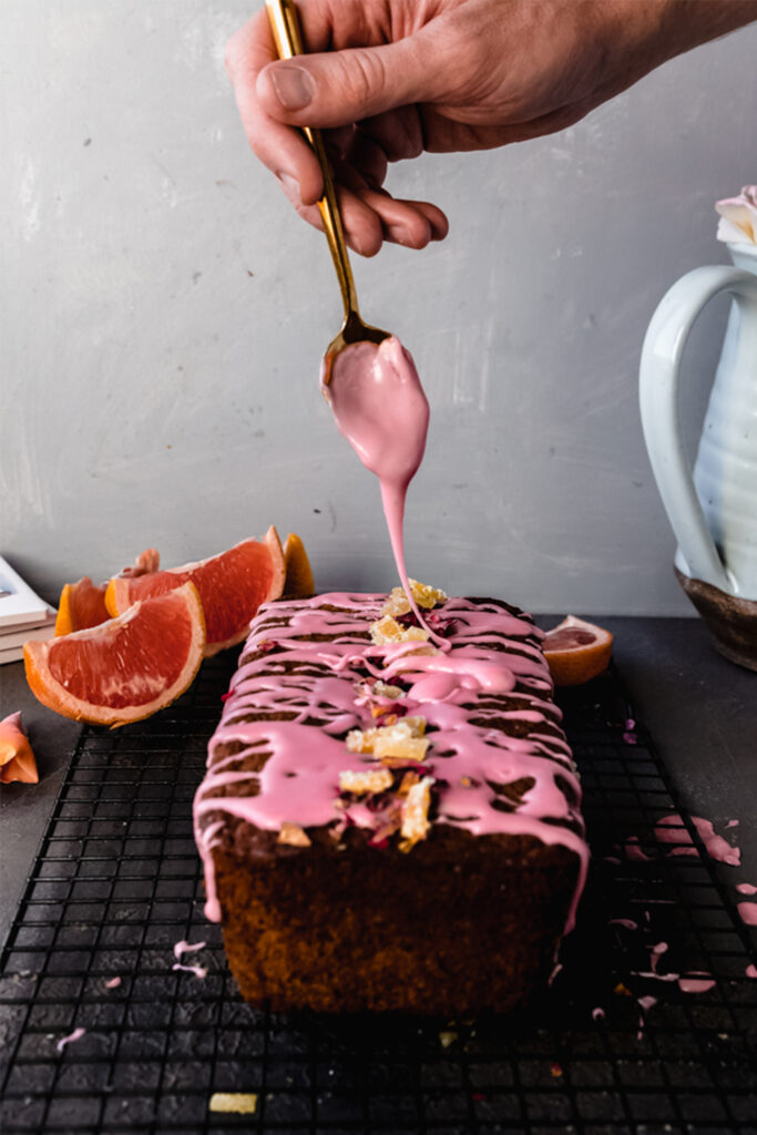 spoon drizzling icing onto vegan grapefruit poppyseed loaf cake