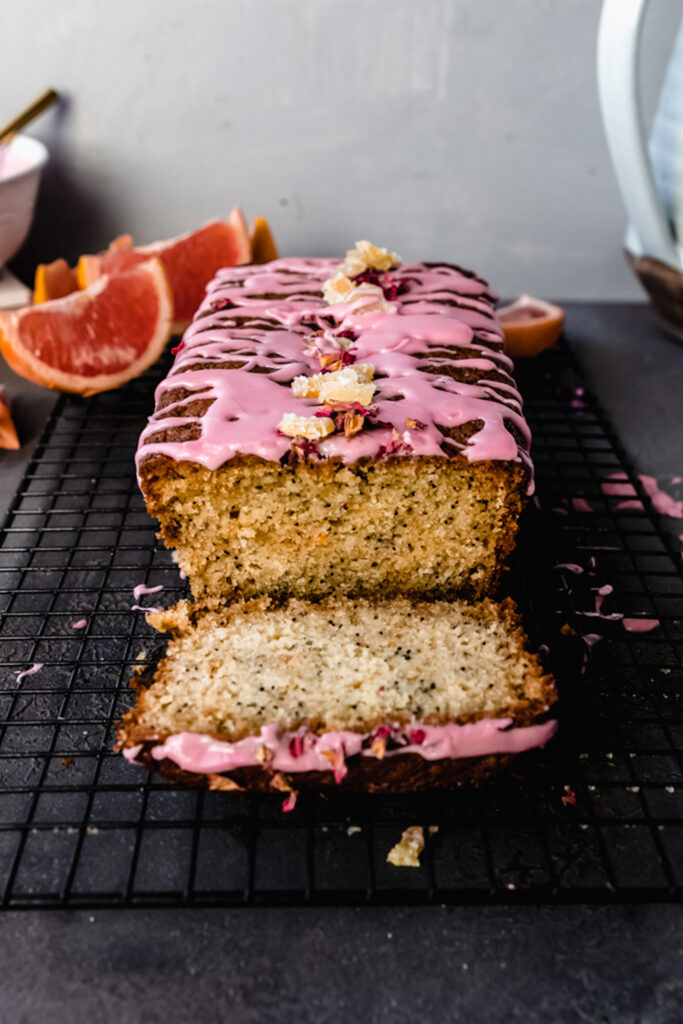 side view of grapefruit poppyseed loaf cake with pink icing and a slice cut out