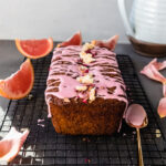 grapefruit poppyseed olive oil loaf cake on a cooling rack with a golden spoon